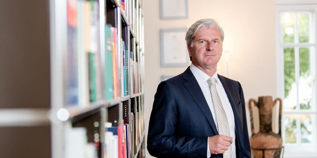 Rechtsanwalt Dr. Klaus Höchstetter in Kanzlei neben Bücherregal
