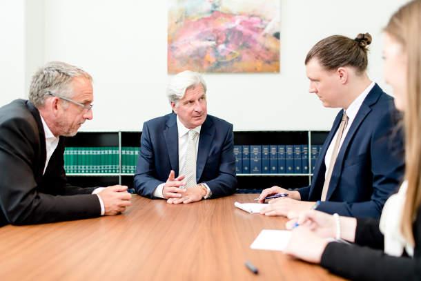 Dr. Höchstetter mit Mandanten am Konferenztisch